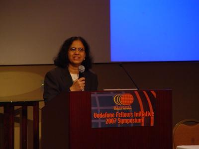 Addressing a gathering at a symposium.